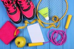 Zapatos rosados del deporte, manzana fresca y accesorios para el deporte en tableros azules, espacio de la copia para el texto en Fotos de archivo