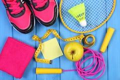 Zapatos rosados del deporte, manzana fresca y accesorios para el deporte en tableros azules, espacio de la copia para el texto en Fotografía de archivo