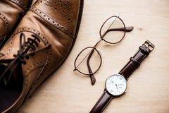 Zapatos, vidrios y reloj de Brown en superficie de madera Fotos de archivo libres de regalías