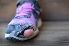 Zapatos viejos con los dedos del pie sin hogar de los agujeros que se pegan hacia fuera Fotos de archivo libres de regalías