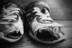 Zapatos viejos con ropa sin hogar lamentable llevada cordones de los agujeros Imágenes de archivo libres de regalías