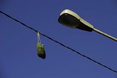 Zapatos viejos que cuelgan de una línea eléctrica con posts de la lámpara Fotografía de archivo libre de regalías