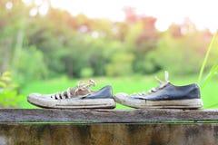 zapatos viejos y sucios con la madera encima de la pared del cemento Imágenes de archivo libres de regalías