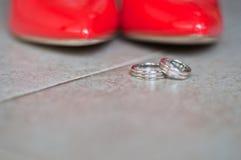 Zapatos y anillos de bodas rojos Fotografía de archivo libre de regalías