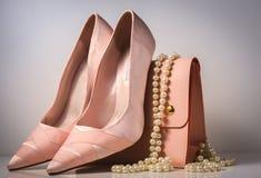 Zapatos y bolso rosados del encanto en fondo gris Fotos de archivo libres de regalías