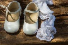 Zapatos y calcetines blancos del ` s de los niños en la madera Foto de archivo libre de regalías