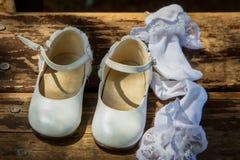 Zapatos y calcetines blancos del ` s de los niños en la madera Fotos de archivo