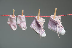 Zapatos y calcetines del bebé en la cuerda para tender la ropa Fotografía de archivo libre de regalías