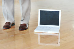 Zapatos y computadora portátil del asunto en suelo Imágenes de archivo libres de regalías