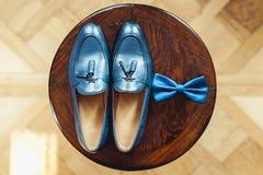 Zapatos y corbata de lazo azules en un taburete redondo de madera Accesorio para el vestido formal Símbolo de la elegancia y de l Imagen de archivo libre de regalías