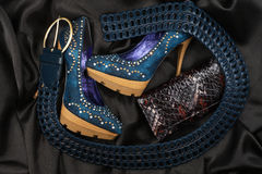 Zapatos y correa azules, monedero que miente en el satén negro Imagen de archivo