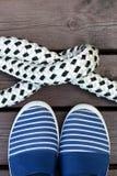 Zapatos y cuerda rayados azules y blancos del estilo del marinero con un nudo en un muelle de madera marrón Fotos de archivo