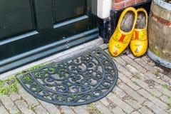 Zapatos y felpudo de madera en la puerta de la casa holandesa vieja Imagen de archivo libre de regalías
