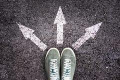 Zapatos y flechas que señalan en diversas direcciones en piso Imagen de archivo libre de regalías