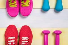 Zapatos y pesas de gimnasia de los deportes para los deportes en un fondo hermoso del amarillo gris Fotos de archivo libres de regalías