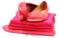 Zapatos y pila femeninos de ropa roja Fondo blanco Fotos de archivo