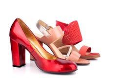 Zapatos y sandalias femeninos rojos, beige y anaranjados con vista lateral de los tacones altos en venta sobre el cierre blanco d fotografía de archivo