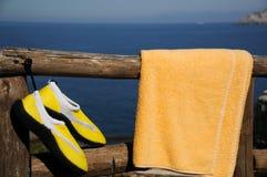 Zapatos y toalla amarillos de la playa Imagenes de archivo
