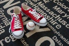 Zapatos y un béisbol en una manta Imagen de archivo libre de regalías