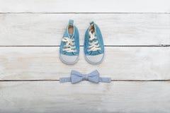 Zapatos y un mariposa-lazo para el muchacho en un fondo de madera VI Imagen de archivo libre de regalías