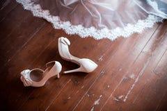 Zapatos y velo blancos de la boda Imagenes de archivo