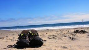 Zapatos y vidrios de sol en la costa Foto de archivo libre de regalías