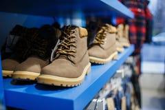 Zapatos - zapatillas de deporte en el estante en la tienda Imagen de archivo