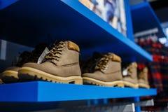 Zapatos - zapatillas de deporte en el estante en la tienda Fotografía de archivo