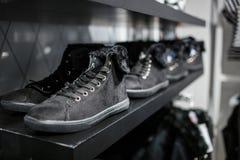 Zapatos - zapatillas de deporte grises en el estante en la tienda Foto de archivo libre de regalías