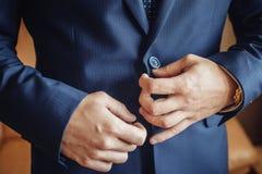 Zapinający kurtkę wręcza zamknięty up Elegancki mężczyzna w kostiumu przymocowywa guziki i prostuje jego kurtki narządzanie wycho zdjęcia stock
