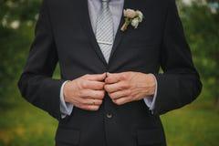 Zapinający kurtkę wręcza zamknięty up Elegancki mężczyzna w kostiumu przymocowywa guziki i prostuje jego kurtkę Przygotowywać dla obrazy royalty free