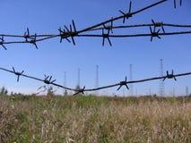 Zapora ciężki drut kolczasty na tle teren zamknięty w radiowy wierza polu obrazy stock