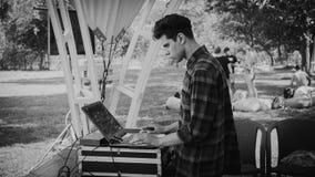 Zaporizhia Ukraina-Augusti 2018: ett pölparti i företagsovohen discjockeyn fokuseras och väljer upp musik, begreppet av arkivbild