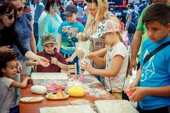 Outdoors children activity on charity family festival. Zaporizhia/Ukraine- June 2, 2018: children and their parents participating at anti-stress toy creation royalty free stock photo