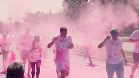 ZAPORIZHZHIA, UKRAINE - APRIL 29, 2018: The organizers throw, throw paint holi, pink, color, in the face of the marathon. Runners who run along the avenue, on stock footage