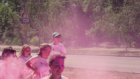 ZAPORIZHZHIA, UKRAINE - APRIL 29, 2018: The organizers throw, throw paint holi, pink, color, in the face of the marathon. Runners who run along the avenue, on stock video