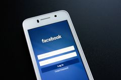 ZAPORIZHZHYA,乌克兰- 2014年11月07日:有Facebook社会网络登录画面的白色巧妙的电话在黑表上 免版税库存图片