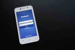 ZAPORIZHZHYA, ΟΥΚΡΑΝΙΑ - 7 ΝΟΕΜΒΡΊΟΥ 2014: Άσπρο έξυπνο τηλέφωνο με την κοινωνική οθόνη σύνδεσης δικτύων Facebook στο μαύρο πίνακ Στοκ φωτογραφία με δικαίωμα ελεύθερης χρήσης