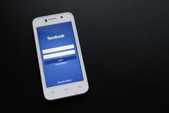 ZAPORIZHZHYA, УКРАИНА - 7-ОЕ НОЯБРЯ 2014: Белый умный телефон с начальным экраном сети Facebook социальным на черной таблице Стоковое фото RF