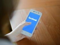 ZAPORIZHZHYA, DE OEKRAÏNE - JANUARI 23, 2015: Jonge Vrouw die Sociale het Netwerktoepassing van Facebook op haar Slimme Telefoon  Royalty-vrije Stock Afbeeldingen