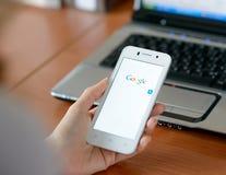 ZAPORIZHZHYA, UCRANIA - 23 DE ENERO DE 2015: Mujer joven que usa búsqueda del web de Google en su teléfono elegante Fotografía de archivo