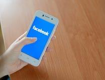 ZAPORIZHZHYA, UCRANIA - 23 DE ENERO DE 2015: Mujer joven que usa el uso social de la red de Facebook en su teléfono elegante Fotografía de archivo