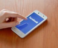 ZAPORIZHZHYA, UCRANIA - 23 DE ENERO DE 2015: Mujer joven que usa el uso social de la red de Facebook en su teléfono elegante Fotos de archivo libres de regalías