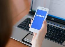 ZAPORIZHZHYA, UCRANIA - 23 DE ENERO DE 2015: Mujer joven que usa el uso social de la red de Facebook en su teléfono elegante Imagen de archivo libre de regalías
