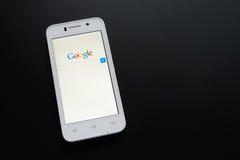 ZAPORIZHZHYA, UCRANIA - 7 DE NOVIEMBRE DE 2014: Teléfono elegante blanco con la búsqueda de Google en la pantalla en la tabla neg Imagen de archivo