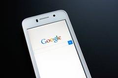 ZAPORIZHZHYA, UCRANIA - 7 DE NOVIEMBRE DE 2014: Teléfono elegante blanco con la búsqueda de Google en la pantalla en la tabla neg Fotos de archivo
