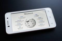 ZAPORIZHZHYA, UCRANIA - 7 DE NOVIEMBRE DE 2014: Teléfono elegante blanco con la página de Wikipedia en la pantalla en la tabla ne Imagen de archivo