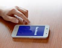 ZAPORIZHZHYA UKRAINA - JANUARI 23, 2015: Ung kvinna som använder Facebook social nätverksapplikation på hennes smarta telefon Royaltyfri Bild