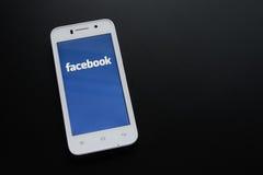 ZAPORIZHZHYA UKRAINA, LISTOPAD, - 07, 2014: Biały Mądrze telefon z Facebook sieci Ogólnospołecznym zastosowaniem na ekranie na cz Zdjęcia Stock