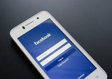 ZAPORIZHZHYA, UKRAINE - 7. NOVEMBER 2014: Weißes intelligentes Telefon mit Anmeldungs-Schirm Facebook-Sozialen Netzes auf schwarz Lizenzfreies Stockbild